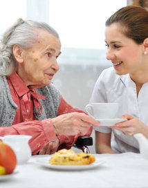 caretaker serving a cup of coffee to an elderly woman