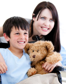 caregiver and child holding a teddy bear in wheelchair smiling