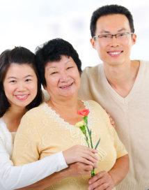 elderly woman holding a flower with her children