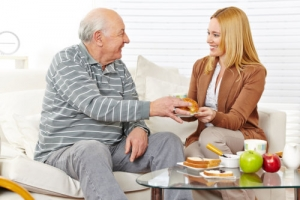 old man with his caregiver eating a breakfast together