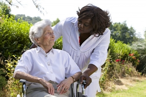 afro-american caregiver talking to disabled senior women outdoors